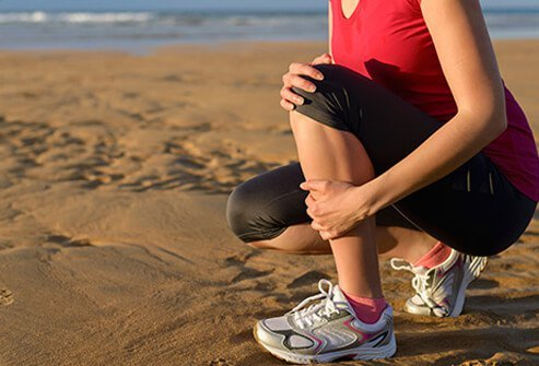 A woman running the beach experiencing shin splints.