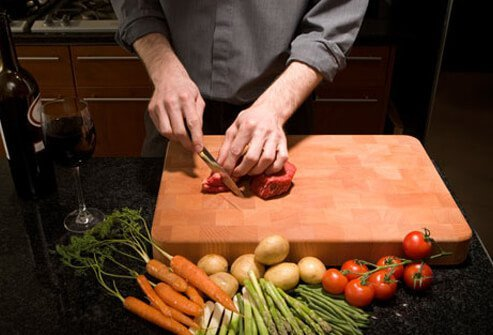 A man cutting food in the kitchen.