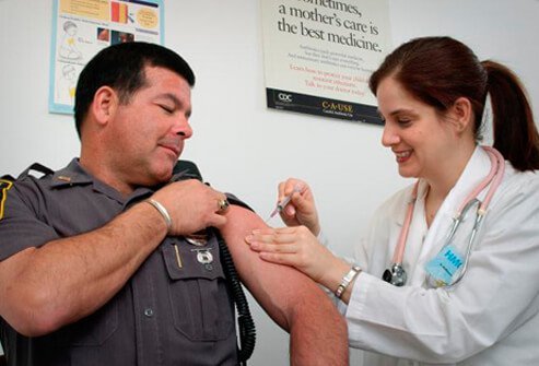 A law enforcement officer receives a swine flu vaccination shot from a nurse.