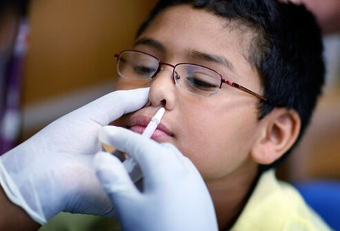 A boy receives a H1N1 nasal flu spray vaccine from a nurse.