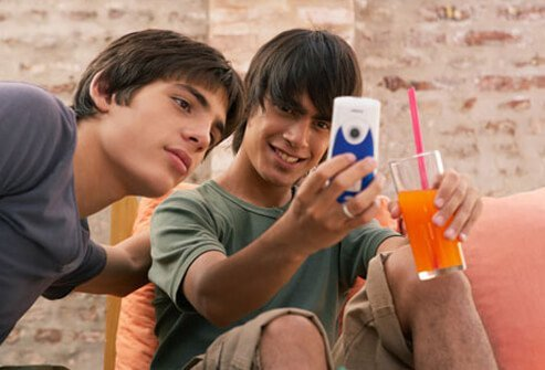 Teen boys share text messages from a cell phone.