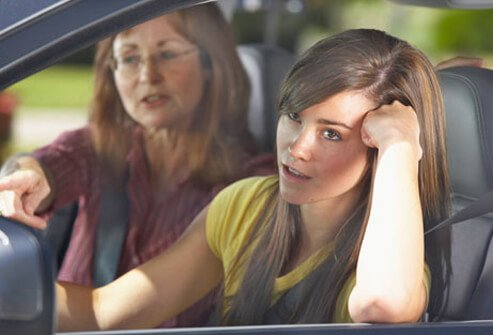 A girl drivesing in a car with her mother.