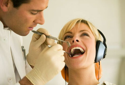 A dentist examining a woman's teeth.