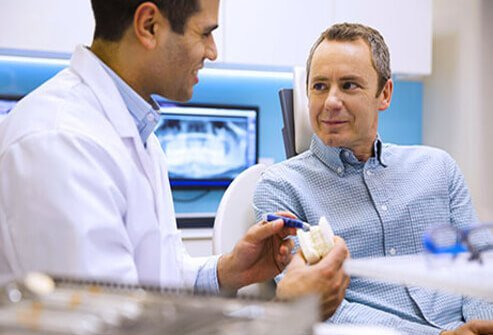 A dentist consults with a patient about teeth whitening options.