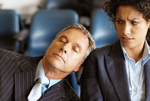 A man with dandruff sleeps on a woman's shoulder.