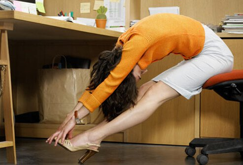 Photo of a woman stretching at her desk.