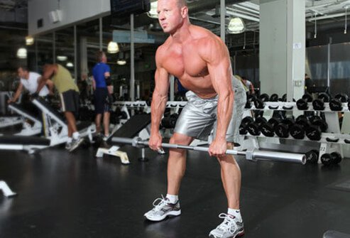 Photo of a trainer doing a Romanian dead lift with a barbell.