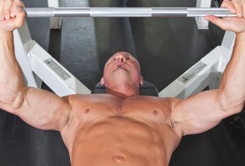 Photo of a trainer showing position for the bench press.