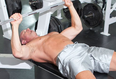 Photo of a trainer doing bench press repetitions.