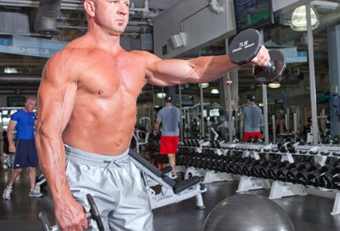 Photo of a man doing a front shoulder raise with dumbbells.