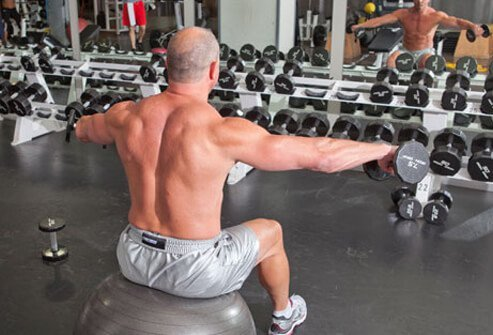 Photo of a man doing a lateral shoulder raise with dumbbells.
