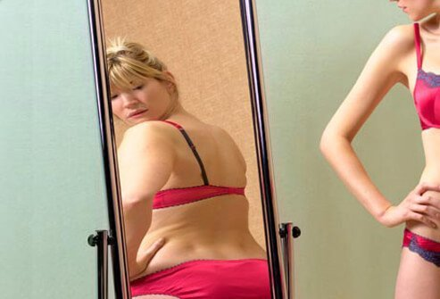 A woman suffers from false body image and looks at her distorted reflection in the mirror.