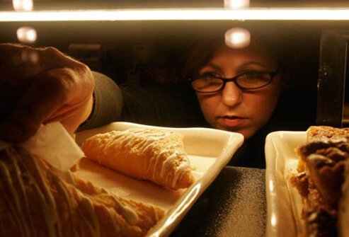A woman binge eats and reaches for a pastry.
