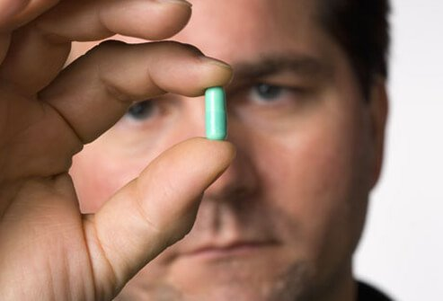 A man holding a capsule.