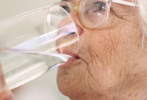 Photo of elderly woman drinking water.