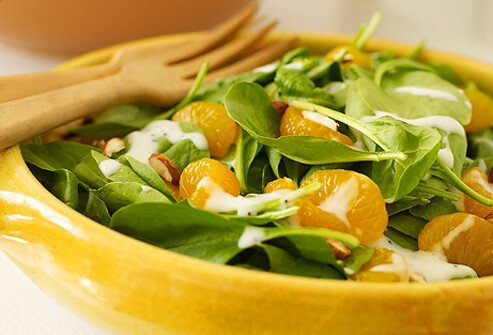 Spinach salad topped with a bit of dressing and mandarin oranges.
