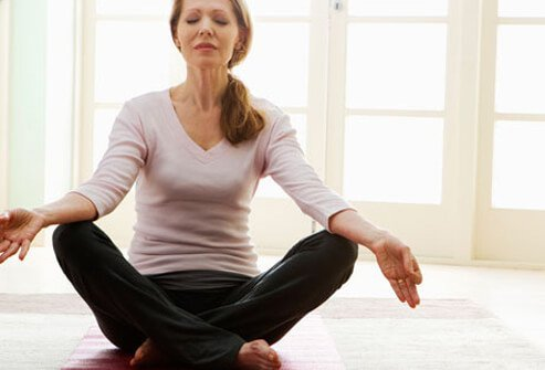 A woman meditates to reduce stress.