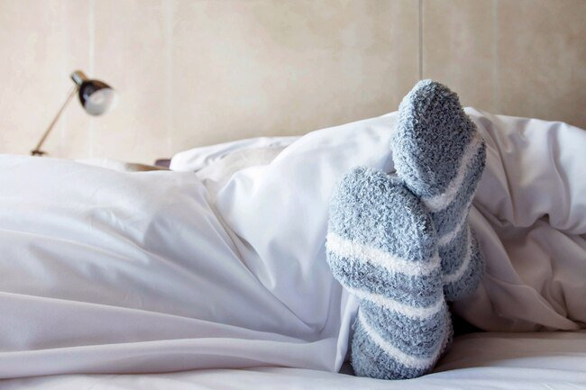 Wearing socks to bed will help keep you toasty at night.