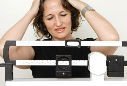 A woman is disappointed after weighing herself.