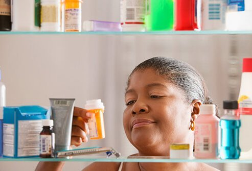 Woman reading medication label in front of medicine cabinet.